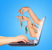 Keys holding in fingers with monitor screen. Hands Royalty Free Stock Photo