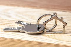 Keys and keychains on wood. Keys and keychains in the shape of a house on a wooden background stock photos