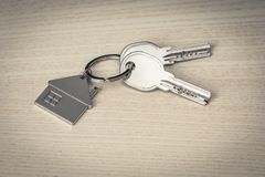 Keys and keychains on wood. Keys and keychains in the shape of a house on a wooden background royalty free stock photography