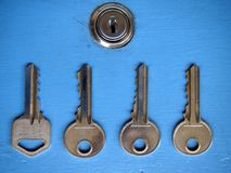 Keys and a keyhole on a blue door Stock Photo