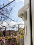 Keys in a keyhole. Of a white PVC door Royalty Free Stock Photo