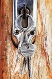 Keys in lock. Set of keys in lock of old wooden door stock photography