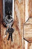 Keys in lock. Set of keys in lock of old wooden door Royalty Free Stock Images