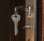 The keys in the lock of a metal door. Close up Royalty Free Stock Photos