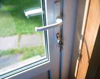 Keys In Door. Keys in a lock of a pvc door, indoor cropped shot stock photos