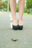 Keys lying on asfalt surface and elegant woman Royalty Free Stock Photo