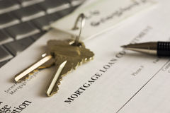 Keys, mortgage statement and pen on a laptop. A bunch of house keys, a mortgage statement and a pen sitting on a laptop keyboard Stock Photos