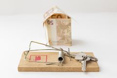 The mortgage trap. Keys in the mousetrap, in the background a house figure made with bills Royalty Free Stock Image