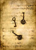 Keys on music sheet. Old keys on an old, yellowed music sheet in grunge Stock Photos