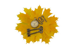 Keys and old pocket watch on a yellow leaves Royalty Free Stock Photography