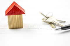 Keys and a pen alongside a model of a house Stock Photo
