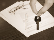 Keys please. Hand holding keys,contract in background Royalty Free Stock Image