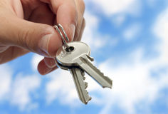 Keys please. Hand holding keys,blue skies with clouds in background royalty free stock photography