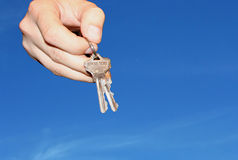 KEYS PLEASE. Hand holding keys, blue skies with clouds in background Stock Photo