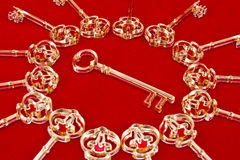 Keys on a red. Golden skeleton keys made of plexiglas on a red background royalty free stock photo