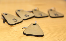 The Keys. Of several rooms of a hostel are on a wooden table. Selective focus Stock Images