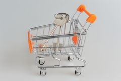 Keys in shopping cart within on gray Royalty Free Stock Photography
