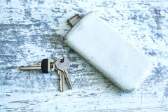 Keys and a smartphone on a wooden table Royalty Free Stock Photo