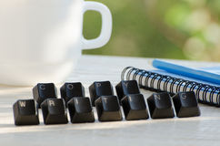Keys on the table, the word copywriting, notebook, pencil, cup, greens in the background Royalty Free Stock Photo