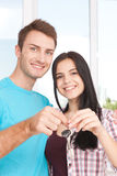Keys of their new house. Cheerful young couple holding key. Stock Photography