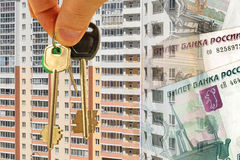 The keys to the apartment on a background of money and houses . Royalty Free Stock Photography