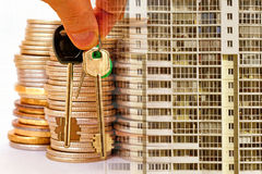 The keys to the apartment on a background of money and houses . The concept of mortgage lending stock photos