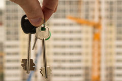 The keys to the apartment in hand on the background of houses Royalty Free Stock Photo