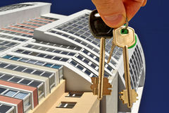 The keys to the apartment in hand on the background of houses Royalty Free Stock Photos