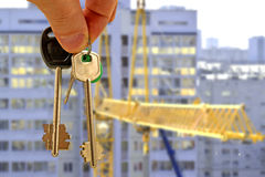 The keys to the apartment in hand on the background of houses Stock Photos