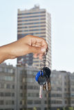 Keys to the apartment. In his left hand against the background of high-rise buildings Royalty Free Stock Image
