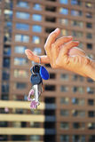 Keys to the apartment. In his left hand against the background of high-rise buildings Royalty Free Stock Photos