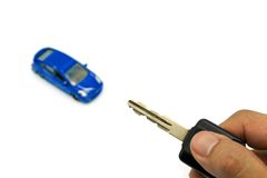 Right hand holding car key and  car model for business concept Royalty Free Stock Image