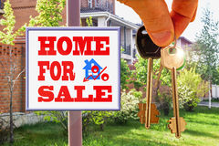 The keys to the house on the background Billboard of sale . Royalty Free Stock Images