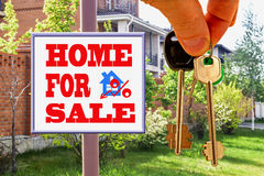 The keys to the house on the background Billboard of sale . Royalty Free Stock Photo