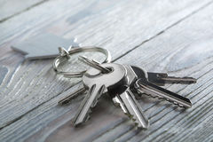 Keys to house with keychain on white wooden background Stock Photos