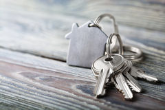 Keys to house with keychain on white wooden background stock photo
