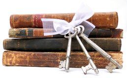 Keys to Knowledge. A stack of antique leather bound books from the seventeen and eighteen hundreds along with a set of vintage keys tied with a white bow Royalty Free Stock Photo