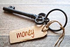 Keys to Money - Concept photo. Keys to Money - Concept photo. Old key with paper label on wooden Old key with paper label on woode. Keys to Money - Concept photo Stock Photos