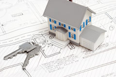 Keys to a New Home. A model house rests on blueprints with keys to the new home Royalty Free Stock Photos
