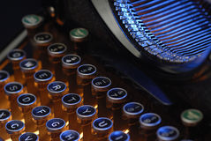 Keys and typebar. Shot closeop on vintage typewriter, lit with orange and blue lights royalty free stock photography