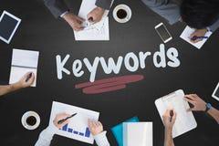 Keywords against blackboard. The word keywords and business meeting against blackboard Royalty Free Stock Photos