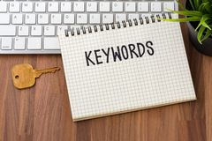 Keywords concept with key and computer. Keywords word on notebook with key and computer on wooden table Stock Image