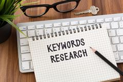 Keywords research concept with computer and key. Keywords research words on notebook with computer keyboard on wooden desk Stock Photo