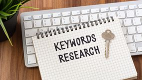 Keywords research with key. Keywords research words on notebook with key computer keyboard Stock Photos