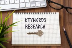 Keywords research word with key. Keywords research for seo concept with computer on wooden desk Stock Image