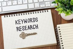 Keywords research for seo concept. With key and computer on wooden desk Royalty Free Stock Photography