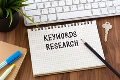 Keywords research words on notebook. With computer on work table Royalty Free Stock Photos