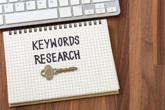 Keywords research on wooden table background. Keywords research words on notebook with key and computer keyboard Stock Photography