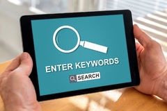 Keywords search concept on a tablet. Male hands holding a tablet with keywords search concept Royalty Free Stock Image