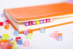 KEYWORDS word on colorful bead block as bookmark in book. Keywords research and content marketing idea concept Stock Photo